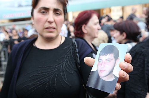 Patima Karosanidze shows at a rally outside the Parliament on May 28 a picture of his 21-year-old son, Demur Managadze, who, she said, is missing since the break up of the protest rally on May 26. She said that her son is an activist of a youth wing of the People's Assembly, an opposition movement which was behind the recent street protests. Photo: Guram Muradov/Civil.ge